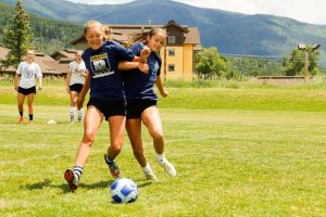 Girls playing soccer in Regis gear